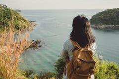 Mulher nova do viajante que está e que olha a vista que aprecia um bea Imagem de Stock