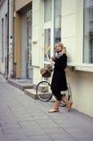 Mulher nova e bicicleta na rua Imagem de Stock Royalty Free