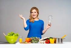 Mulher nova e bonita da dona de casa que cozinha em uma cozinha Imagens de Stock Royalty Free