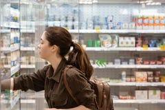 A mulher nova e bonita obtém o produto necessário do refrigerador no departamento da leiteria foto de stock royalty free