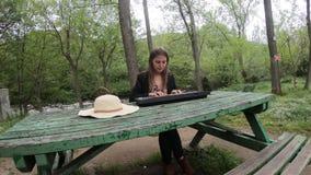 Mulher nova e bonita que joga o sintetizador na tabela de um parque, França video estoque