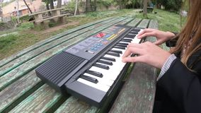 Mulher nova e bonita que joga o sintetizador na tabela de um parque, França vídeos de arquivo