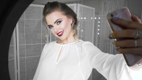 Mulher nova e bonita que toma a imagem do selfie com telefone celular na frente da lâmpada do anel, tiro do estúdio filme