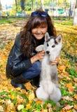 Mulher nova e cão de puxar trenós siberian do cão pequeno Fotos de Stock Royalty Free