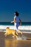 Mulher nova e cão que funcionam na praia Foto de Stock Royalty Free