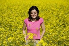 Mulher nova e campo de flor amarelo Fotografia de Stock Royalty Free