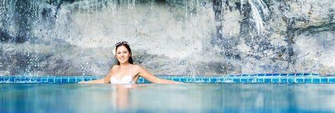 Mulher nova e desportiva no roupa de banho Menina que relaxa em uma associação no verão imagens de stock