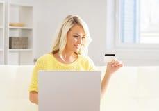 Mulher nova e feliz com um cartão de crédito Conceito em linha da compra fotografia de stock