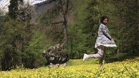 A mulher nova e feliz está em uma área da conservação durante a florescência na mola video estoque