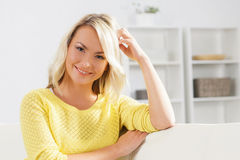 Mulher nova e feliz que descansa no sofá em casa imagens de stock royalty free