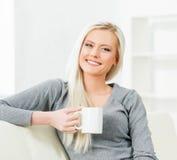 Mulher nova e feliz que descansa no sofá em casa com café fotos de stock
