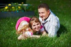 Mulher nova e homem felizes na grama verde fotos de stock