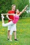 Mulher nova e instrutor que fazem exercícios Fotografia de Stock Royalty Free