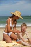 Mulher nova e menino na praia Fotografia de Stock