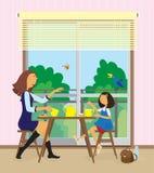 A mulher nova e sua filha têm um pequeno almoço. Foto de Stock