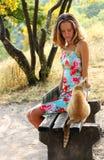 Mulher nova e um gato que senta-se no banco Fotos de Stock