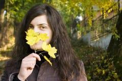 Mulher nova e uma folha do outono Imagens de Stock