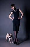 Mulher nova elegante com um cão do pug no estúdio Fotos de Stock Royalty Free