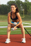 Mulher nova em Dumbbells da terra arrendada do sutiã dos esportes no banco fotografia de stock royalty free