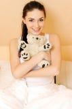 Mulher nova em sua cama com urso de peluche Foto de Stock Royalty Free