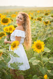 Mulher nova em um campo dos girassóis luz do por do sol no campo dos girassóis Fotografia de Stock Royalty Free