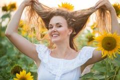 Mulher nova em um campo dos girassóis luz do por do sol no campo dos girassóis Imagem de Stock