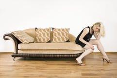 Mulher nova em um sofá imagens de stock