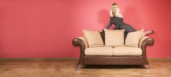 Mulher nova em um sofá foto de stock