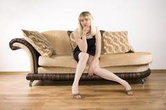 Mulher nova em um sofá fotos de stock royalty free