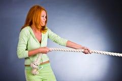 A mulher nova em um terno dos esportes puxa uma corda Foto de Stock Royalty Free