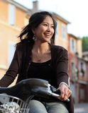Mulher nova em uma bicicleta foto de stock