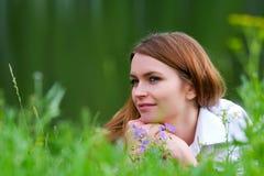 Mulher nova em uma grama. Imagens de Stock