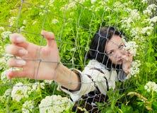 Mulher nova em uma grama que olha sobre a cerca de fio fotos de stock