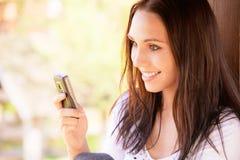 A mulher nova encantadora lê sms Imagem de Stock Royalty Free