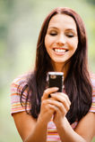 A mulher nova encantadora lê sms Imagens de Stock Royalty Free