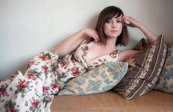 Mulher nova encantadora no sofá Foto de Stock Royalty Free