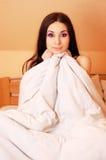 Mulher nova engraçada que senta-se na cama Foto de Stock