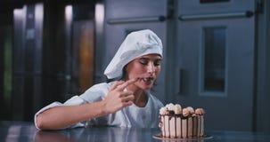 Mulher nova entusiasmado de sorriso do padeiro em uma padaria industrial da cozinha ela que prova o creme do bolo cozido fresco filme