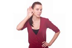A mulher nova escuta com cuidado sussurro ou bisbolhetice Foto de Stock Royalty Free