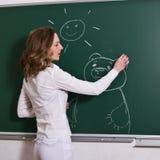 A mulher nova está desenhando em um quadro-negro. Imagem de Stock Royalty Free