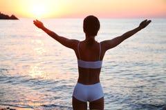 A mulher nova está feliz na praia foto de stock