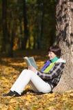 A mulher nova está lendo Imagem de Stock