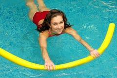 A mulher nova está nadando com macarronete foto de stock