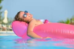 A mulher nova está nadando na cama de ar cor-de-rosa fotos de stock royalty free
