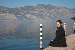 A mulher nova está sentando-se no banco do lago Garda Imagem de Stock Royalty Free