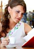 A mulher nova está sentando-se no café Imagens de Stock Royalty Free