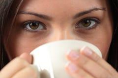 A mulher nova está tendo seus chá/café fotografia de stock royalty free