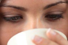A mulher nova está tendo seus chá/café Fotografia de Stock