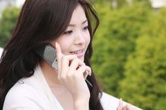 A mulher nova fala com um telefone móvel Fotografia de Stock