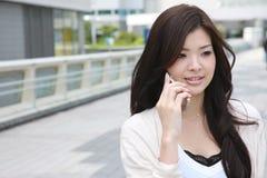 A mulher nova fala com um telefone móvel Fotografia de Stock Royalty Free